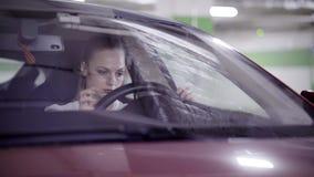 A mulher bonito nervosa vestida na camisa branca senta-se no carro vermelho atrás do volante video estoque