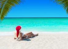 Mulher bonito no banho de sol do chapéu de Santa do Natal no arenoso tropical Fotografia de Stock