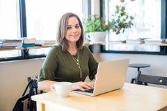 Mulher bonito no café com portátil imagens de stock royalty free