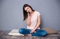Mulher bonito nova que senta-se no assoalho Imagem de Stock Royalty Free
