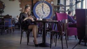 A mulher bonito nova que usa o telefone, sentando-se em um café que guarda um smartphone, respondendo texts Mulher de negócio bon vídeos de arquivo