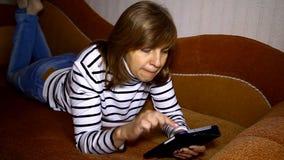 Mulher bonito que encontra-se no sofá que olha na tabuleta video estoque