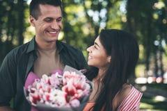 A mulher bonito que gira para seu noivo após a obtenção floresce dele foto de stock royalty free