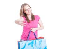 Mulher bonito que guarda sacos de compras e que mostra o número quatro Imagens de Stock