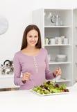 Mulher bonito que mistura uma salada que está na cozinha fotos de stock