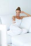 Mulher bonito que presta atenção à tevê no sofá Fotografia de Stock
