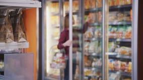 A mulher borrada está abrindo a porta de vidro do refrigerador e do alimento de obtenção seguro da prateleira vídeos de arquivo