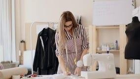 Mulher branca 30 anos de vendedor novo talentoso idoso que levanta na mesa do trabalho, craftswoman do alfaiate em costurar a ofi video estoque