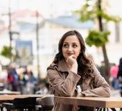 Mulher branca bonita nova com cabelo marrom encaracolado, na perspectiva da rua fotografia de stock