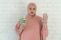 Mulher branca com olhos azuis em um hijab cor-de-rosa que guarda um ros?rio e d?lares em um fundo branco fotografia de stock