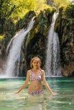 Mulher branca nova em um roupa de banho que espirra a água em uma cachoeira bonita imagem de stock
