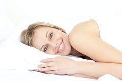 Mulher brilhante que relaxa em sua cama Imagens de Stock