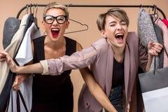A mulher brincalhão da gritaria dois está tentando comprar coisas com venda competi??o imagem de stock