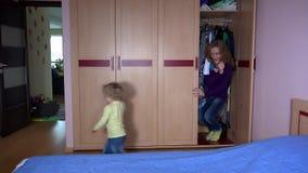 A mulher brincalhão e sua menina da filha saem do armário e da corrida afastado vídeos de arquivo
