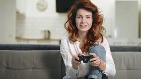 Mulher brincalhão que tenta ganhar o jogo de vídeo na cozinha aberta video estoque