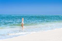 A mulher bronzeada bonita no roupa de banho está andando na praia do oceano fotografia de stock
