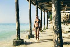 A mulher bronzeada nova anda ao longo do por do sol do oceano do litoral foto de stock royalty free