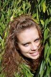 Mulher Brown-haired atrás das folhas verdes Foto de Stock