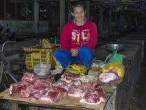 Mulher Bucher que vende a carne no mercado Foto de Stock