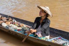 Mulher burmese no barco de madeira longo pequeno que vende lembranças, trinkets e bijouterieat que a flutuação introduz no mercad Fotos de Stock