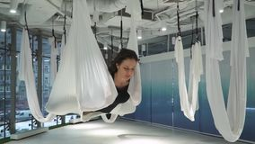 Mulher calma nova atrativa que pendura na rede da ioga no fitness center moderno Muitas redes brancas que penduram ao redor filme