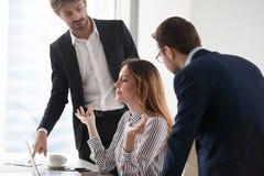 Mulher calma nova que medita no local de trabalho, ignorando colegas fotografia de stock