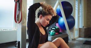 A mulher cansada e concentrada levanta os cabelos acima e relaxado após um exercício duro no gym que é fora do quando da energia video estoque