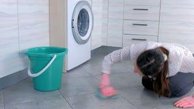 A mulher cansada em luvas de borracha cor-de-rosa lava e fricciona a mancha no assoalho da cozinha com um pano Telhas cinzentas n