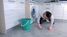 A mulher cansada em luvas de borracha cor-de-rosa lava o assoalho da cozinha com um pano Telhas cinzentas no assoalho filme