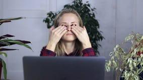 Mulher cansada, fazendo massagens seus olhos, aliviando o esforço do muito tempo do trabalho e olhando a tela do portátil vídeos de arquivo