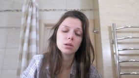 A mulher cansado acordada no banheiro estala-se nos mordentes para acordar video estoque