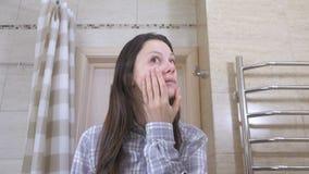 Mulher cansado acordada no banheiro que olha sua reflexão no marror e nas tentativas para pôr-se em ordem vídeos de arquivo