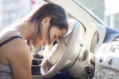 Mulher cansado adormecida no volante em seu carro Imagem de Stock