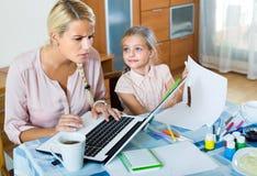Mulher cansado com a filha que trabalha em linha Fotografia de Stock Royalty Free