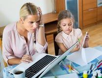 Mulher cansado com a filha que trabalha em linha Fotografia de Stock