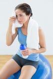 Mulher cansado com a toalha em torno do pescoço e waterbottle na bola do exercício Fotografia de Stock Royalty Free