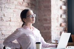 Mulher cansado da virada que sofre da dor lombar na mesa de escritório imagem de stock