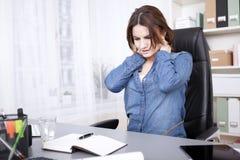 Mulher cansado do escritório que faz massagens a parte traseira de seu pescoço imagens de stock