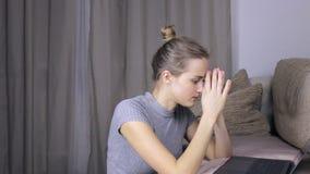 Mulher cansado e virada que usa seu portátil em casa filme