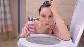 A mulher cansado grávida está vomitando no toalete que senta-se no assoalho em casa e que olha a câmera filme