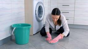 Mulher cansado no assoalho de borracha cor-de-rosa da cozinha das lavagens das luvas com um pano e olhares na câmera Telhas cinze