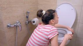 A mulher cansado nova grávida está vomitando no toalete que senta-se no assoalho e na água potável filme