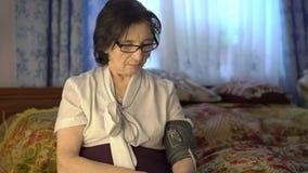 A mulher cansado pôs a ferramenta da medida da pressão sanguínea sobre sua mão vídeos de arquivo