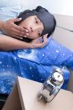 Mulher cansado que boceja na cama imagem de stock