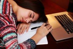 Mulher cansado que dorme na tabela Fotos de Stock Royalty Free