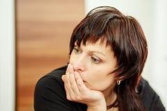 Mulher cansado que guarda a cabeça, olhando para fora Imagens de Stock