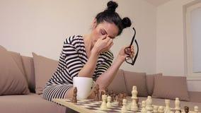 Mulher cansado que joga a xadrez video estoque