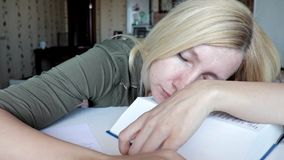 Mulher cansado que senta-se pela tabela e que dorme, com uma cabe?a em um livro, em uma educa??o e em um conceito grandes do estu video estoque