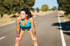 Mulher cansado que sua após a corrida na estrada Fotografia de Stock Royalty Free