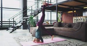 Mulher carismática em casa que pratica a ioga que faz o relaxamento meditando exercícios para o corpo, na manhã para carregar vídeos de arquivo